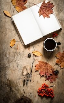 秋のスタイル。熱い一杯のコーヒーで本を開きます。木製の背景に。
