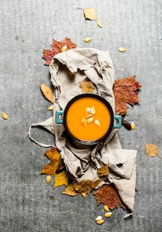 Autumn style. pumpkin soup from a ripe pumpkin on stone table.