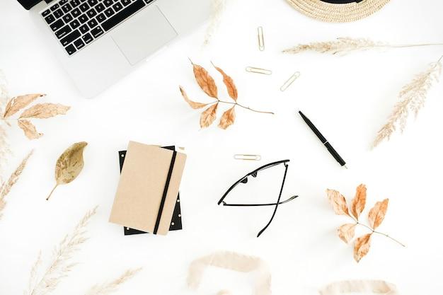 秋のスタイリッシュなホーム オフィスのワークスペース、ラップトップ、乾燥した紅葉、白い背景にわら。フラットレイ、トップビュー