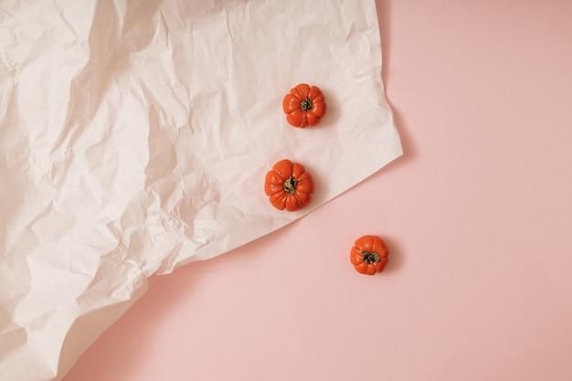 カボチャ、トマトと秋の太陽に照らされたピンクと白の背景。フラットレイ収穫またはハロウィーンの概念。カラフルな野菜のクリエイティブなレイアウト。スペースをコピーします。