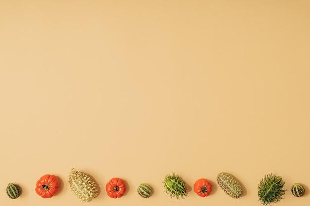 カボチャ、サイサリス、トマト、緑の季節の果物と秋の太陽に照らされた黄色の背景。フラットレイ収穫またはハロウィーンの概念。カラフルな野菜のクリエイティブなレイアウト。スペースをコピーします。