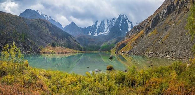曇り空の下の大きな山から高原の谷の小川と美しい浅い山の湖と秋の日当たりの良い高山の風景。アルタイのアッパーシャブリン湖。