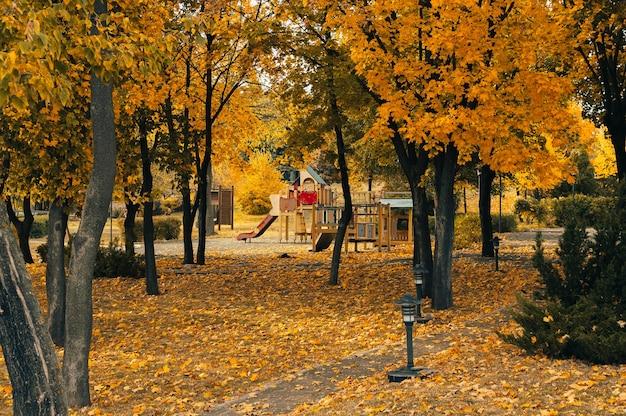 Осенний солнечный пейзаж. дорога в парке к детской площадке