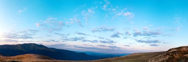 Осенняя панорама горы восхода солнца с луной в небе. изображение сшивается тремя кадрами.