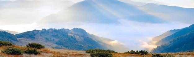 Осенний восход солнца с видом на горы с солнечным лучом и дымкой. составное изображение из трех кадров.
