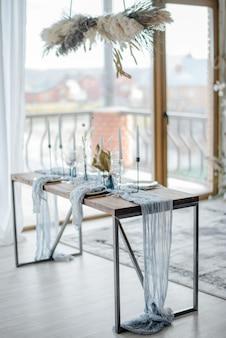 Осеннее украшение стола, деревянный стол подается с сухоцветом, белая тарелка, винтажные столовые приборы, канделы с ярко-синей марлевой скатертью. вид сверху, выборочный фокус.