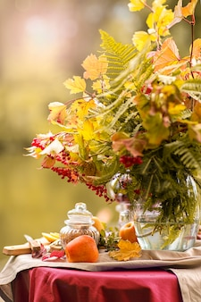 Autumn. a table set on the banks of the lake decorated with a bouquet of autumn leaves. tea party. fruit teas with lemon, apples.