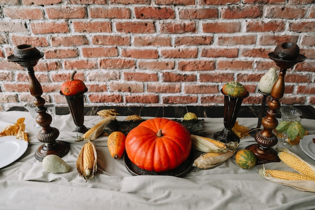 カボチャとキャンドルで感謝祭の秋のテーブルセッティング