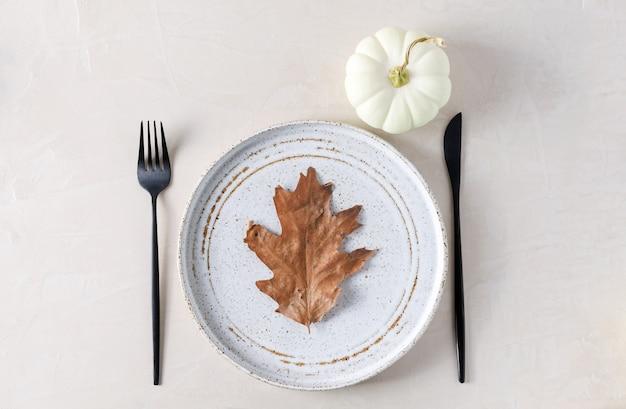 ベージュの背景に秋のテーブルセッティング、プレート、電化製品、カボチャ