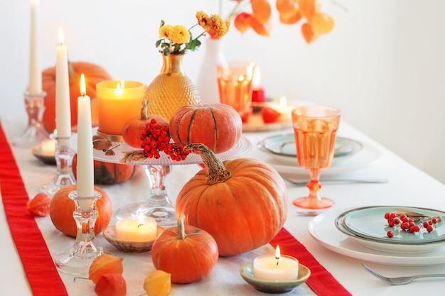 Осенняя сервировка стола с зажженными свечами и тыквами