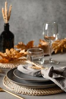 乾燥した黄色のオークの葉と秋のテーブルセッティング、グレーの秋の装飾。