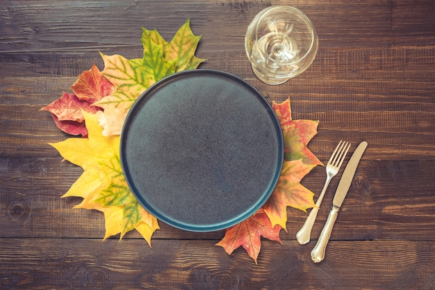Сервировка стола осени с упаденными листьями на деревянном столе.