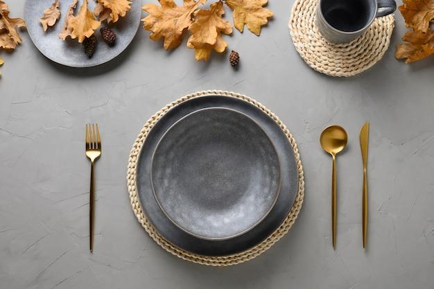秋のテーブルセッティング、季節の収穫とグレーのゴールドの装飾。
