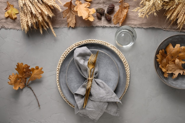 Autumn table setting with seasonal harvest and gold decor on grey.