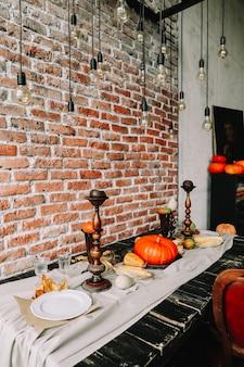 お祝いのディナーのためのカボチャとキャンドルと秋のテーブル