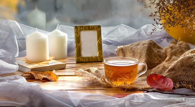 Autumn tea composition with a cup of tea, photo frame and candles. home comfort. family.