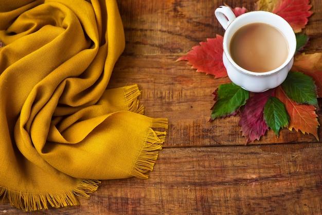 가을 차 컵 구성, 노란색 스카프, 나무 배경에 leafs. 텍스트에 대 한 장소 복사 공간 가 배경입니다. 따스하고 포근한 가을 분위기. 플랫 레이, 레이아웃