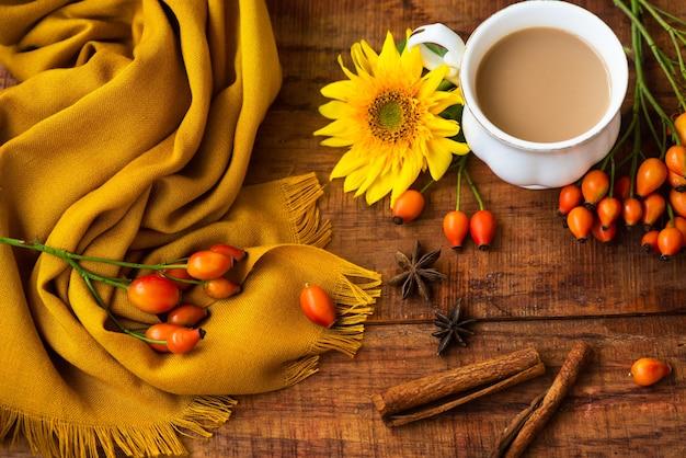 Осенняя композиция чашки чая, желтый шарф, ягоды розы и цветок подсолнуха на деревянном фоне