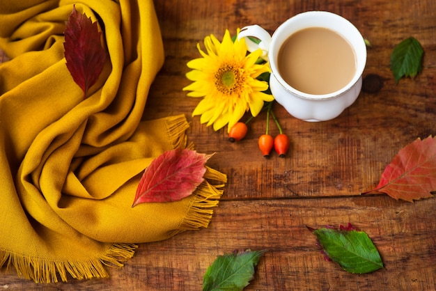 Autumn tea cup composition, yellow scarf, rose berries and sunflower flower on a wooden background. autumn background. warm, cozy atmosphere of autumn. flat lay, layout