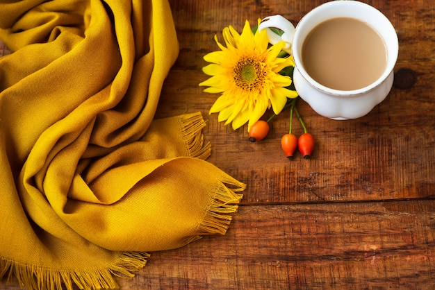 Autumn tea cup composition, yellow scarf, rose berries and sunflower flower on a wooden background