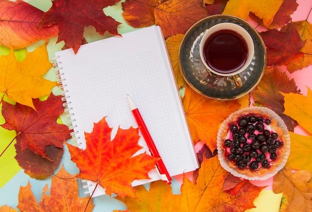 Autumn tea dessert and notebook on autumn leaves