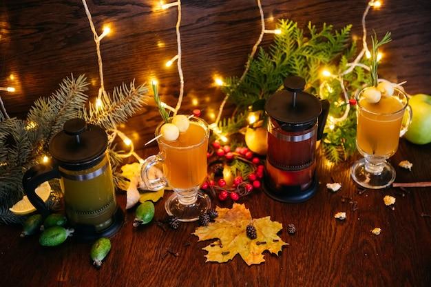 프랑스 언론의 가을 차와 레스토랑의 테이블에 사과, feijoa 및 열매가 들어간 투명한 머그잔에 감귤류 차