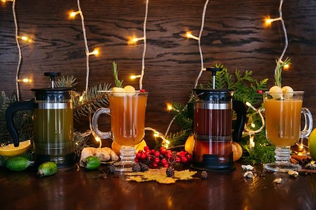 Осенний чай во френч-прессе и цитрусовый чай в прозрачной кружке с яблоком, фейхоа и личи на столе в ресторане
