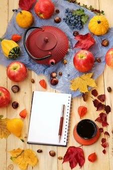 Autumn tea. notebook with red teapot, cup with tea, maple leaves, chestnuts, apples, pumpkin.