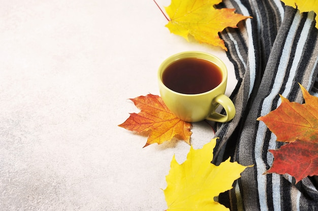 Осеннее чаепитие - чашка чая на фоне кленовых листьев и шерстяной шарф.