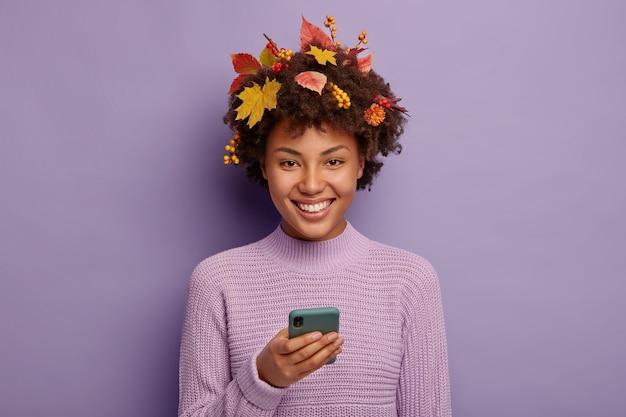 가을, 기술 개념. 행복한 아프리카 계 미국인 여자는 현대 스마트 폰을 사용하고 기꺼이 미소 짓고 단풍으로 장식 된 곱슬 머리를 가지고 있습니다.