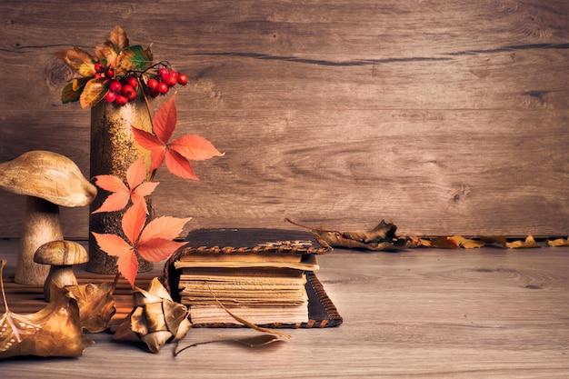 木製のキノコと秋の感謝祭の配置。秋の葉、リンゴ、ピーマン、栗。秋の静物アレンジメント室内、古い木製のテーブル、コピースペースに古いアンティークの本。