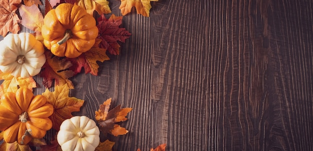 Autumn and thanksgiving background decoration from dry leaves,red berries and pumpkin on dark wooden background.
