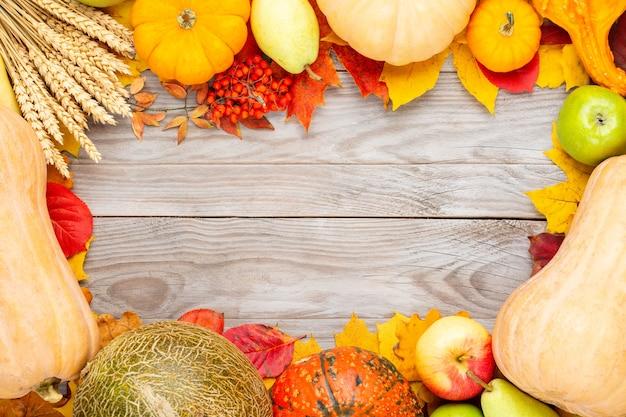 カボチャ、ライ麦、メロン、リンゴ、梨、木製のテーブルの上の色とりどりの葉と秋の感謝祭の背景。テキストのコピースペースを含む上面図