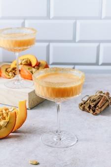 가을, 추수감사절 칵테일. 돌 테이블에 계피와 호박 마가리타 또는 마티니.