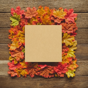 Autumn thanksgiving day background with maple leaves frame on table wood