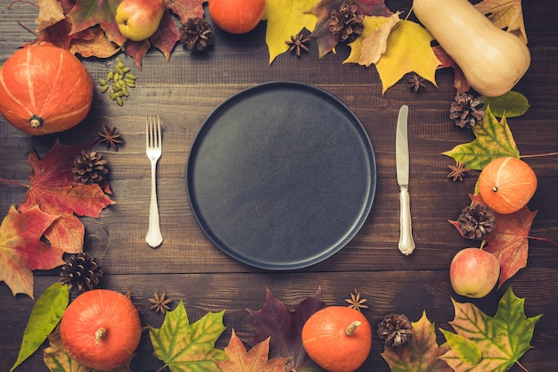 Autumn and thanksgiving day table setting with fallen leaves, pumpkins, spices, empty black platter and vintage cutlery on brown wooden table. top view, .