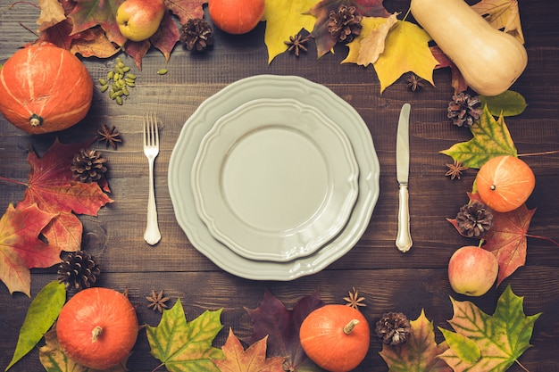 Autumn and thanksgiving day table setting with fallen leaves, pumpkins, spices, grey plate and cutlery on brown wooden table. top view, .