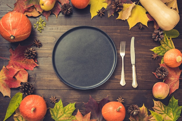 Autumn and thanksgiving day table setting with fallen leaves.