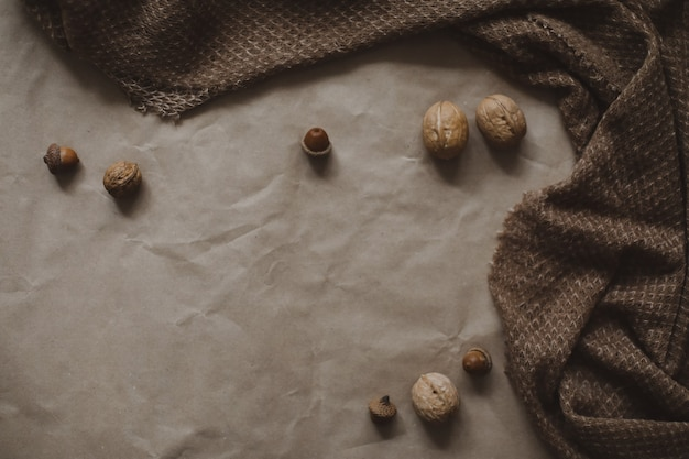 Autumn theme, brown paper texture background with cozy warm plaid, walnuts and acorns, top view, copyspace.