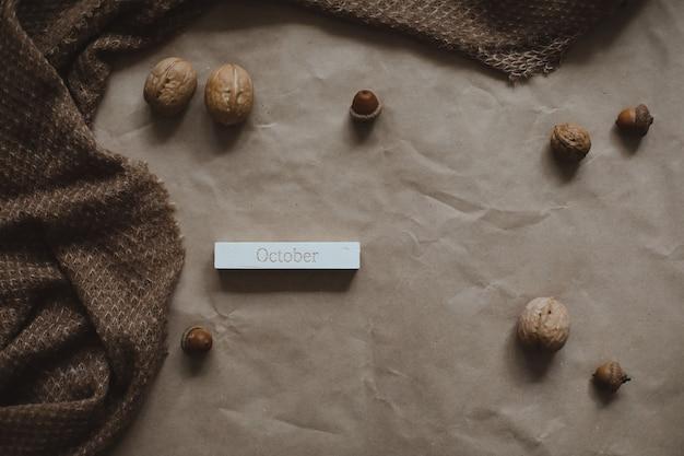 Осенняя тема текстуры коричневой бумаги фон с уютными теплыми клетчатыми грецкими орехами и желудями вид сверху copyspace