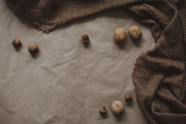 Осенняя тема, коричневый фон текстуры бумаги с уютным теплым пледом, грецкими орехами и желудями, вид сверху, copyspace.