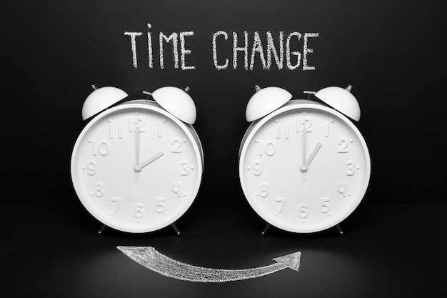 Autumn time change fall back concept . two vintage clocks with chalky text on blackboard