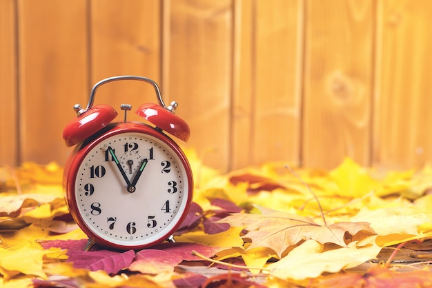 Autumn time change. fallen leaves and old alarm clock on rustic wooden table