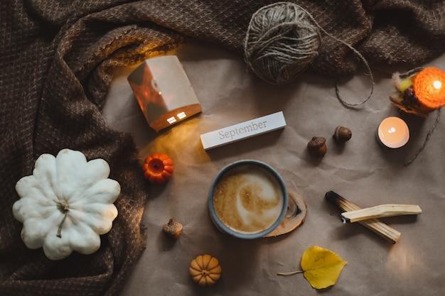 Осеннее время уютный домашний декор hygge с чашкой, свечами, клетчатой хэллоуин и концепцией благодарения