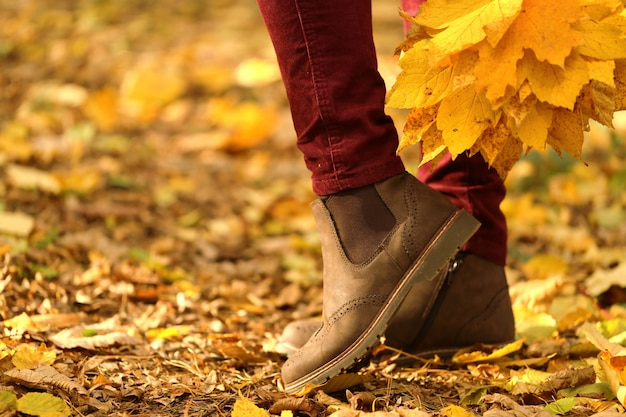Autumn time. female legs in brown suede boots on a yellow leaves. fashionable autumn shoes