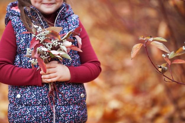 秋の時間。雪の果実のカラフルな葉の花束を持っている女の子の手。コピースペース