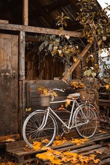 가을 시간. 가을철에는 오래된 대기 시골집의 나무 벽에 기대어 바구니에 다채로운 꽃을 넣은 빈티지 자전거, 가을 수확물이 문에 걸려 있는 끈 가방
