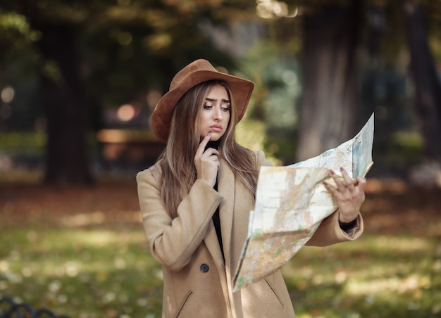 Autumn tourism. young attractive female traveler is guided by the city map