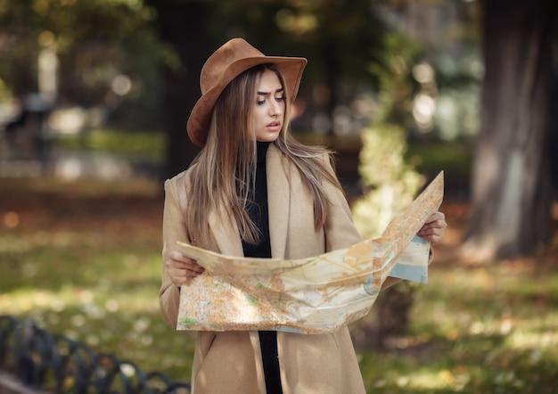 秋の観光。若い魅力的な女性旅行者は、市内地図に案内されています。