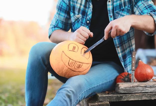 秋の伝統と休日のハロウィーンの準備。自然の中の家、カボチャで作られたランプがテーブルで切り取られています。
